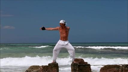 healthy man doing pilates yoga meditation on beach summer