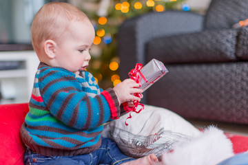 Cute baby opening a Christmas gift