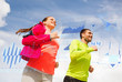 smiling couple with earphones running outdoors