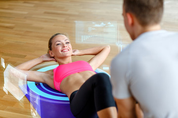 smiling woman with male trainer exercising in gym