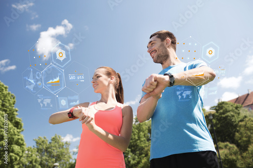canvas print picture smiling couple with heart rate watches outdoors