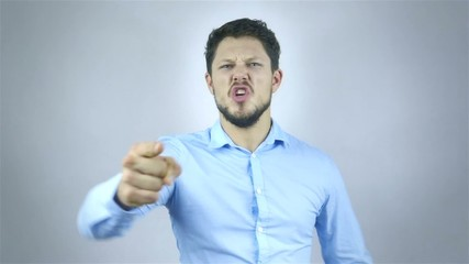 Portrait Of Angry Young Man Shouting Over Grey Background