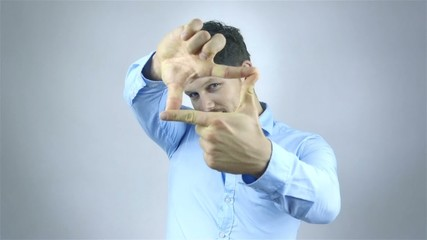 Young man doing a frame with his hands