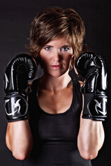Portrait of a beautiful fighter woman in boxing gloves