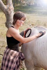 Beautiful woman brushing a horse