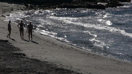 people walking along the beach