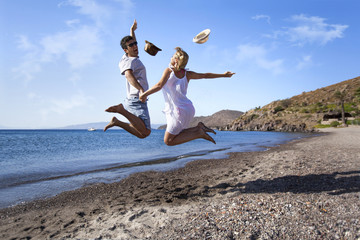 Young couple is jumping on the beach hand to hand