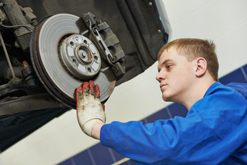 auto mechanic at car brake shoes eximining