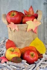 Jute zak met appels en herfstbladeren