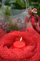 candela rossa accesa e decorazioni natalizie
