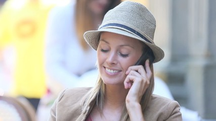 Cheerful modern girl in coffee shop talking on phone