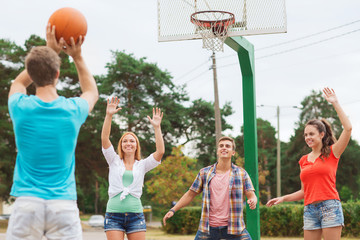 group of smiling teenagers playing basketball