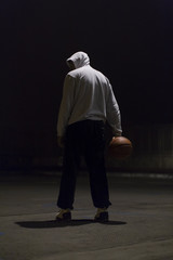 Hooded basketball player holding a ball in one hand