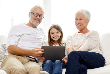 smiling family with tablet pc at home
