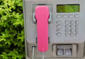 Silver public telephone with pink terminal