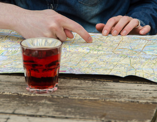 Girl checking city map outside on a table with drink