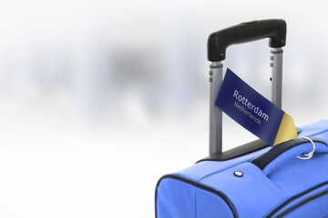 Rotterdam, Netherlands. Blue suitcase with label at airport.