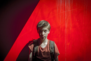 portrait of a teenager boy with rucksack in front of a red wall,