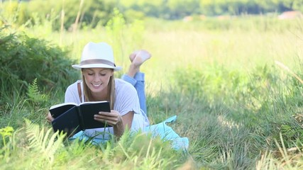 Smiling woman laying in grass and reading book