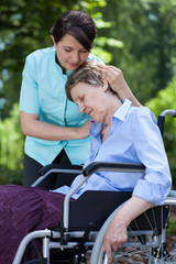 Nurse comforting an old woman on wheelchair