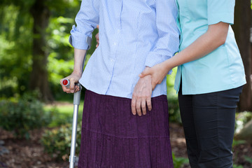 Nurse walking with a female patient with a crutch