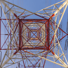 High power transmission towers against blue sky.
