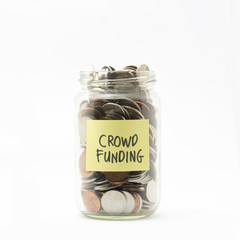 Isolated coins in jar with crowd funding label - financial conce