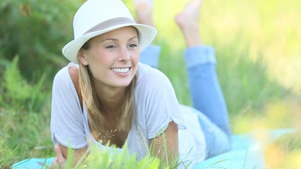 Smiling woman laying in grass and relaxing