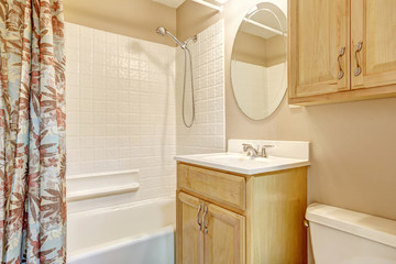 Light beige bathroom with wooden cabinets and floral curtain