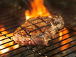 beef steak cooking over flaming grill - 70329885