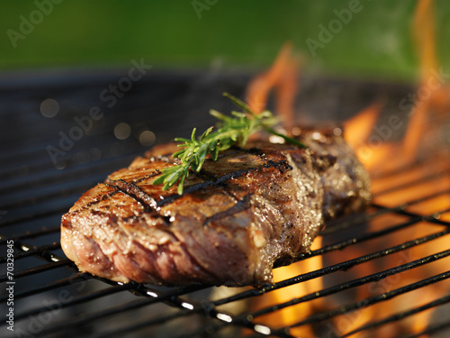 Aluminium Barbecue steak with flames on grill with rosemary