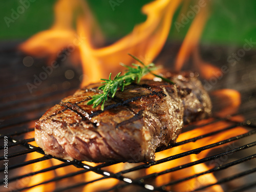 Fotografiet steak with flames on grill with rosemary