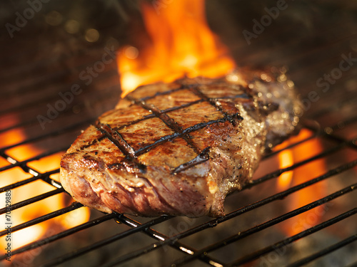 Poster beef steak cooking over flaming grill