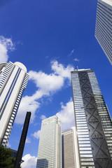 [東京都市風景]青空に流れる白い雲と新宿高層ビル街を見上げる