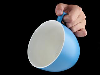 Woman hand holding an gentle blue color cup - mug on black backg