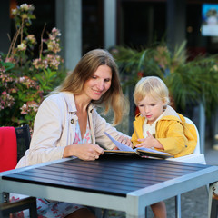 Mother and little daughter relaxing in outdoors cafe