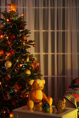 Decorated Christmas tree on home interior background at night