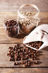 Coffee beans in fabric bag and glass jars on wooden background