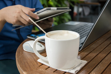 man with a cup of coffee working on his laptop
