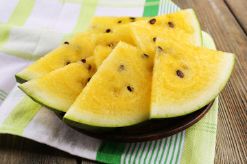 Slices of yellow watermelon on napkin on wooden background