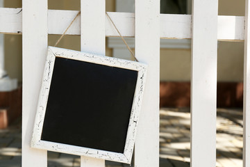Signboard hanging on wooden fence