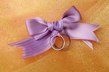 Wedding rings tied with ribbon on color fabric background