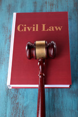 Civil Law book with hammer on wooden table