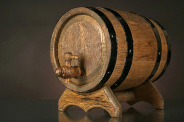 Barrel on wooden table on dark background