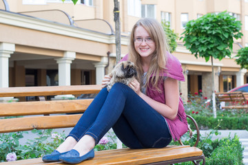 girl with a dog on a bench