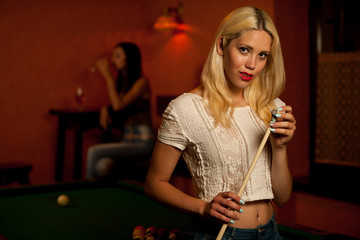 Beautiful young blonde woman playing billiard in a bar