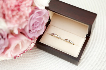 Wedding white gold rings in a box on the bridal bouquet backgrou