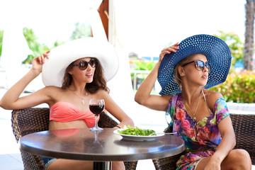 Девушки в солнечных очках в уличном кафе