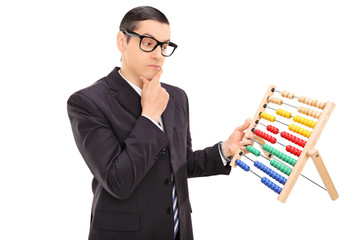 Pensive businessman looking at an abacus
