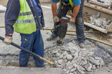 Roadworks construction workers using a jackhammer and shovel